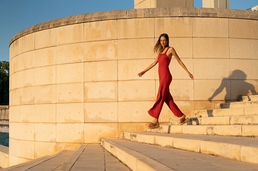 Spain, Barcelona, Montjuic, young woman wearing red jumpsuit walking on stairs - gettyimageskorea