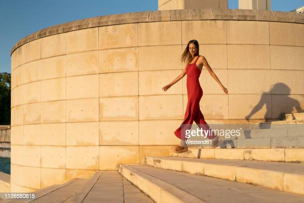 spain, barcelona, montjuic, young woman wearing red jumpsuit walking on stairs - fashion stock-fotos und bilder