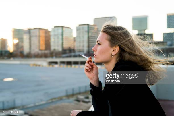 spain, barcelona, pensive young woman smoking cigarette - femme qui fume photos et images de collection