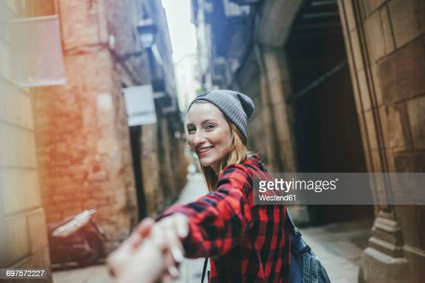 Spain, Barcelona, portrait of smiling young woman holding hands at Gothic Quarter