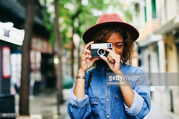 Spain, Barcelona, portrait of smiling young woman wearing hat and denim shirt taking picture with camera