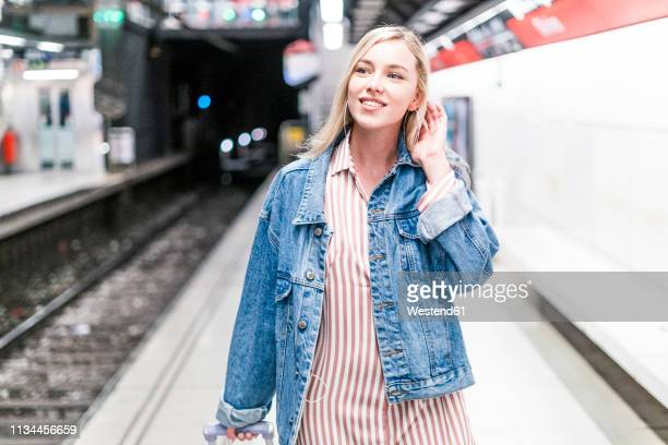spain, barcelona, portrait of smiling young woman with trolley bag at - blouse stock pictures, royalty-free photos & images