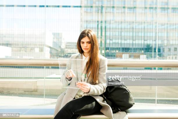 spain, barcelona, portrait of young businesswoman using futuristic portable device at station - three quarter length stock pictures, royalty-free photos & images