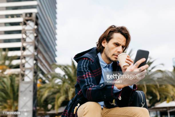 spain, barcelona, serious man sitting in the city with takeaway coffee and cell phone - suspicion stock pictures, royalty-free photos & images