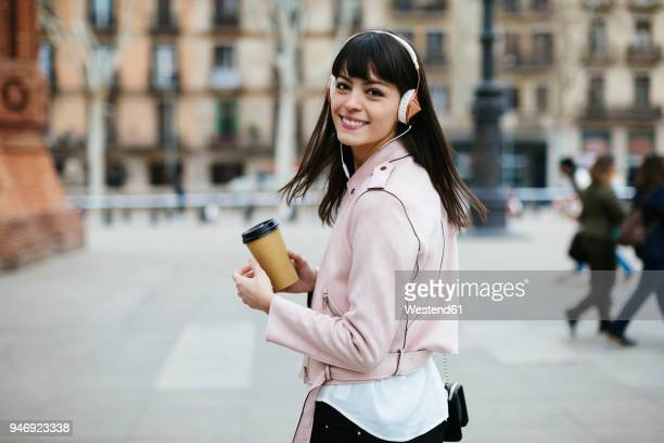 spain, barcelona, smiling woman with coffee and headphones in the city - tourner photos et images de collection