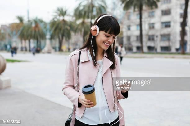 spain, barcelona, smiling woman with coffee, cell phone and headphones in the city - geração millennial imagens e fotografias de stock