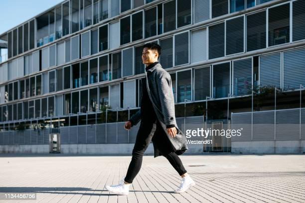 spain, barcelona, smiling young man walking down the street - un seul homme photos et images de collection