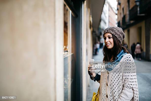 Spain, Barcelona, smiling young woman in the city looking at shop window