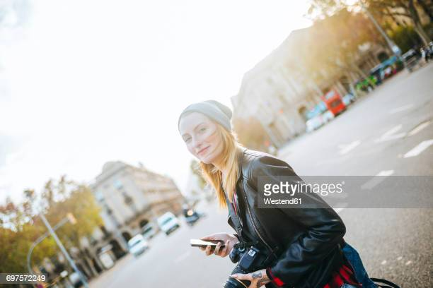 Spain, Barcelona, smiling young woman with mobile phone on the street