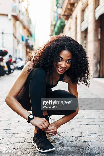 spain, barcelona, sportive young woman tying her shoe - black alley stock photos and pictures