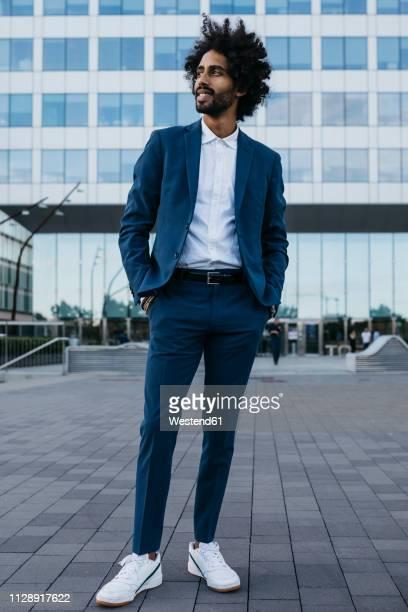 spain, barcelona, stylish young businessman standing in the city - wegsehen stock-fotos und bilder