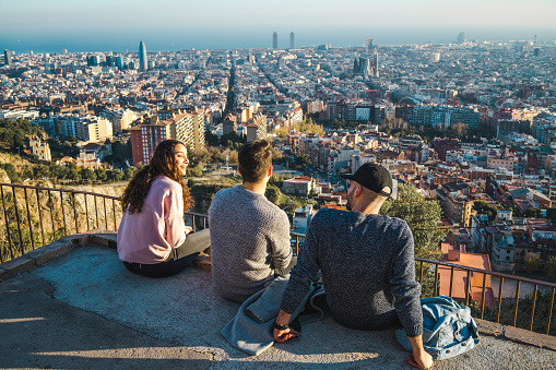 Spain, Barcelona, three friends sitting on a wall overlooking the city - gettyimageskorea
