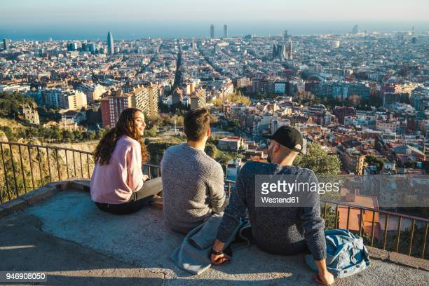 spain, barcelona, three friends sitting on a wall overlooking the city - katalonien stock-fotos und bilder