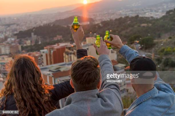 Spain, Barcelona, three friends with beer bottles on a hill overlooking the city at sunset