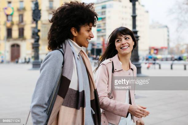 spain, barcelona, two happy women walking in the city - black coat stock photos and pictures