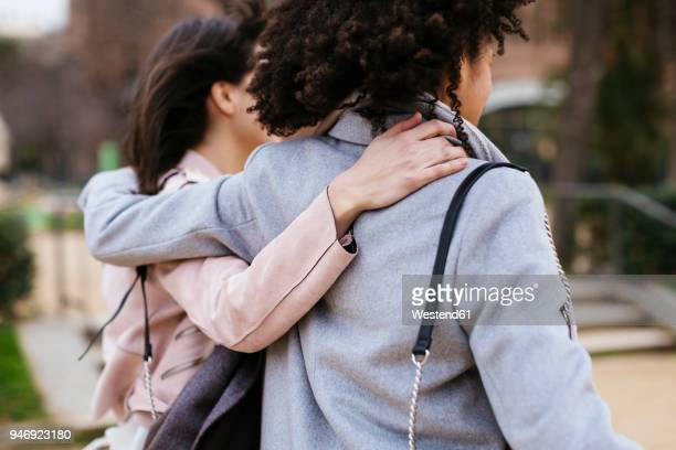 spain, barcelona, two women in city park embracing - arm around stock pictures, royalty-free photos & images