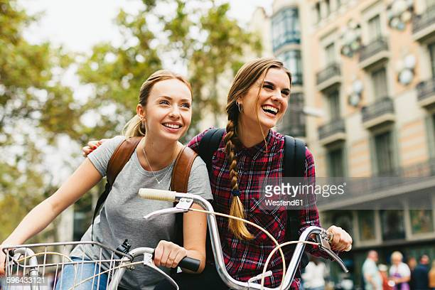 Spain, Barcelona, two young women on bicycles in the city
