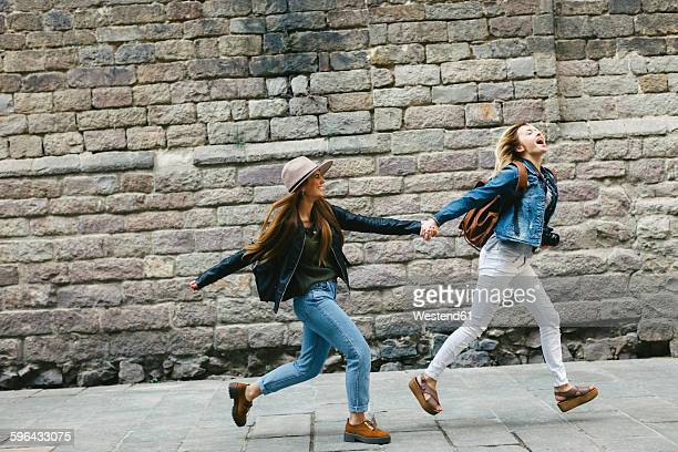 Spain, Barcelona, two young women running hand in hand in the city