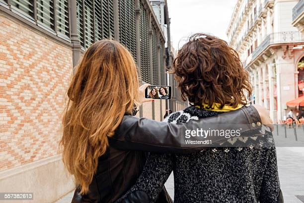 Spain, Barcelona, two young women taking a selfie on the street with smartphone
