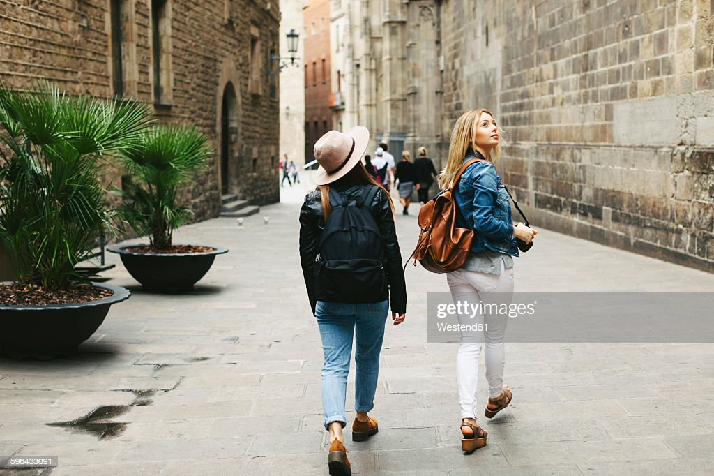 Spain, Barcelona, two young women walking in the city : Stock Photo