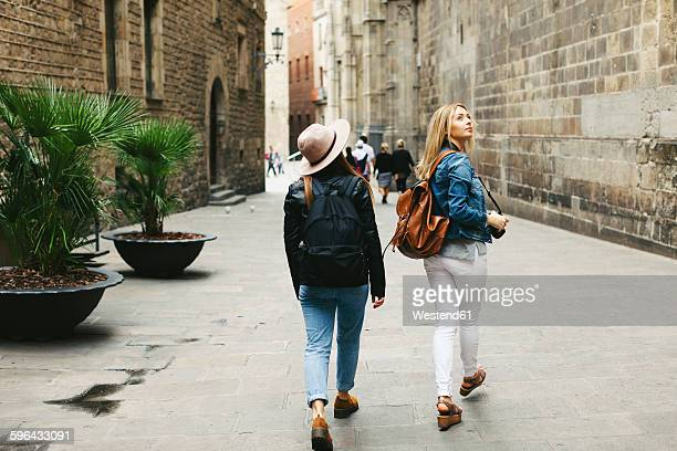 spain, barcelona, two young women walking in the city - toerisme stockfoto's en -beelden
