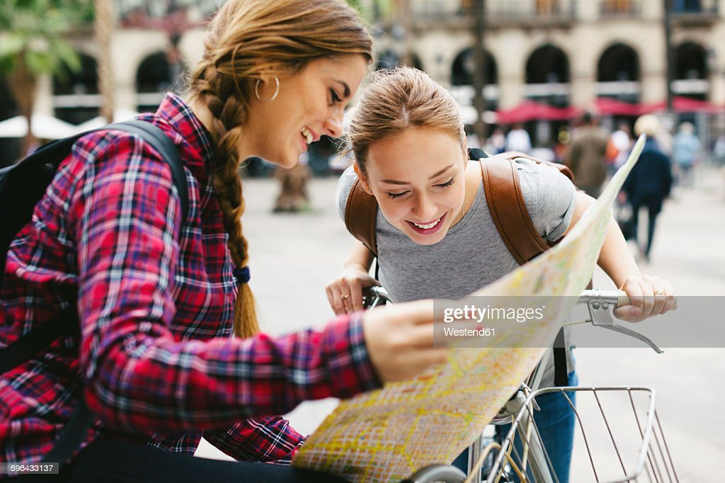 Spain, Barcelona, two young women with map on bicycles in the city : Stock Photo