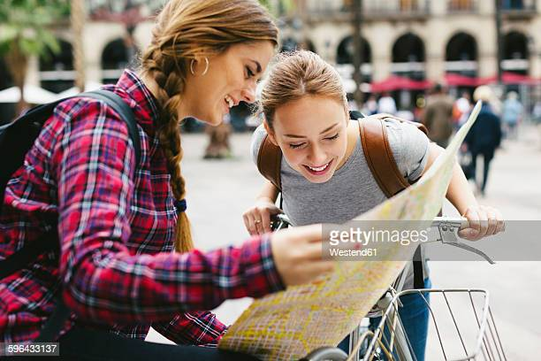 Spain, Barcelona, two young women with map on bicycles in the city