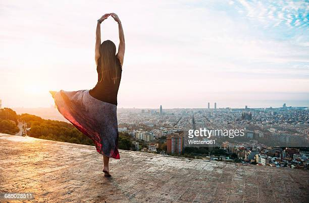 Spain, Barcelona, Woman ldancing at view point over city