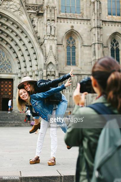 Spain, Barcelona, woman taking picture of two playful young women in the city in the city