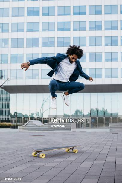 spain, barcelona, young businessman doing skateboard tricks in the city - vestido azul fotografías e imágenes de stock