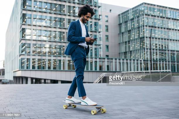 spain, barcelona, young businessman riding skateboard and using cell phone in the city - elegante kleidung stock-fotos und bilder