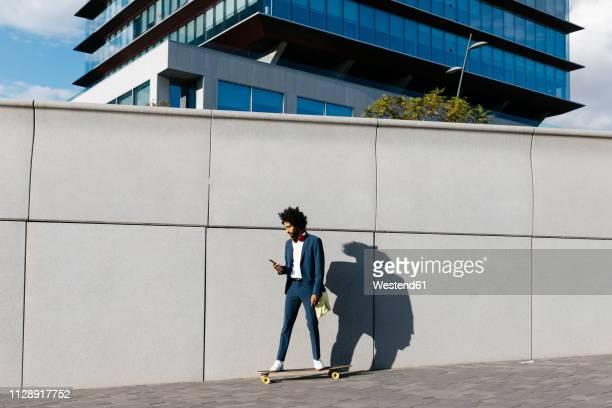 spain, barcelona, young businessman riding skateboard and using cell phone in the city - eislauf oder rollschuhlauf stock-fotos und bilder