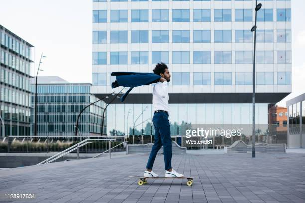 spain, barcelona, young businessman riding skateboard in the city - velocidad fotografías e imágenes de stock