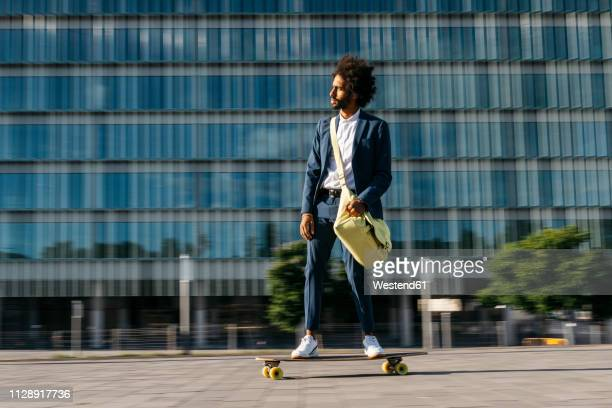 spain, barcelona, young businessman riding skateboard in the city - mouvement photos et images de collection