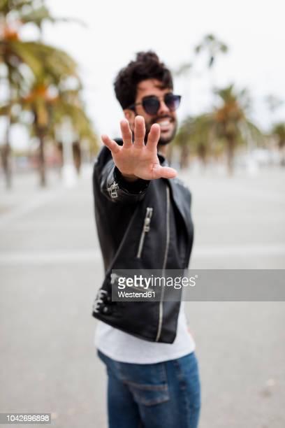spain, barcelona, young man on promenade with palms raising his hand - レザージャケット ストックフォトと画像