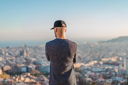Spain, Barcelona, young man standing on a hill overlooking the city - gettyimageskorea