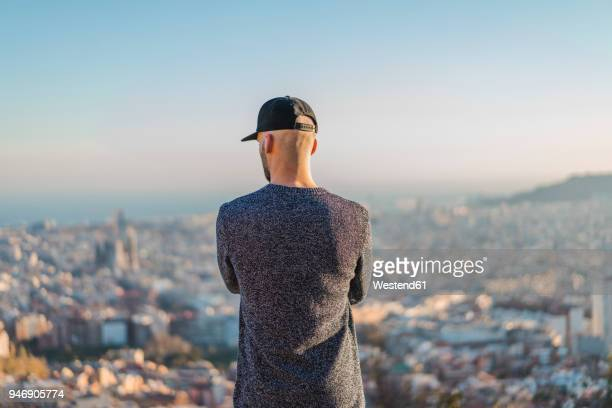 spain, barcelona, young man standing on a hill overlooking the city - horizonte fotografías e imágenes de stock