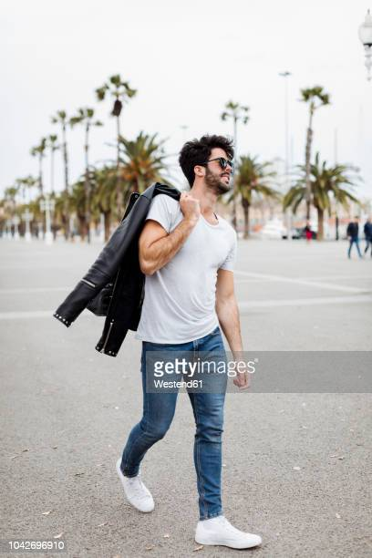 Spain, Barcelona, young man walking on promenade with palms
