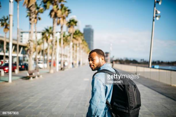 spain, barcelona, young man with backpack walking on beach promenade - tourner photos et images de collection