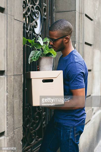 Spain, Barcelona, young man with cardboard box in front of entry door