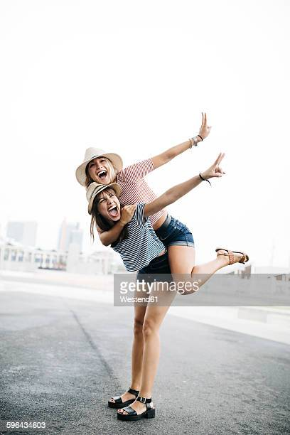 Spain, Barcelona, young woman giving her friend a piggyback ride