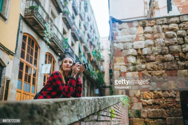 Spain, Barcelona, young woman taking pictures with camera at Gothic Quarter