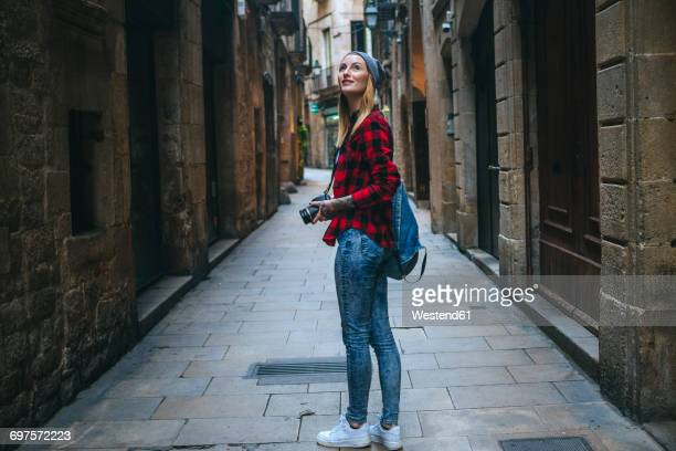 Spain, Barcelona, young woman taking pictures with reflex camera at Gothic Quarter