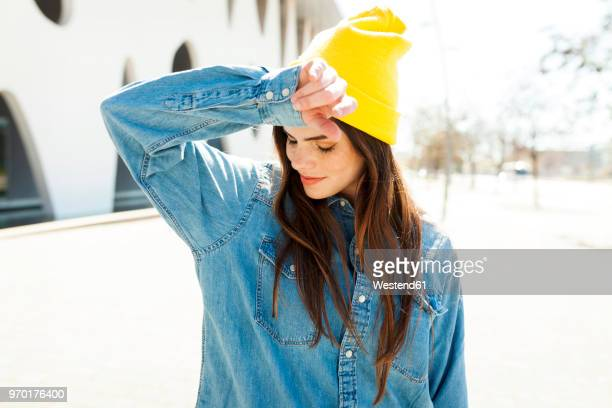 Spain, Barcelona, young woman wearing yellow cap and denim shirt