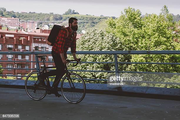 Spain, Bilbao, man riding racing cycle on a bridge