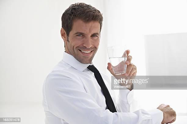Spain, Businessman holding water glass, smiling, portrait