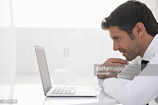 Spain, Businessman thinking while looking laptop, smiling