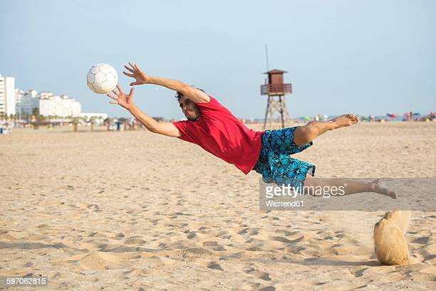 spain, cadiz, el puerto de santa maria, man playing soccer on the beach - ビーチサッカー ストックフォトと画像