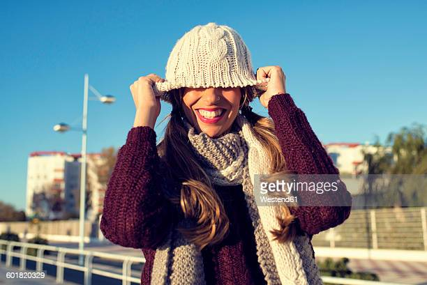 Spain, Cadiz, El Puerto de Santa Maria, playful woman covering her face with wooly hat