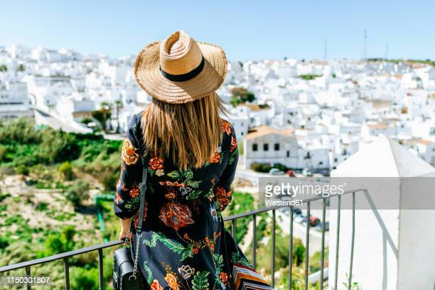 spain, cadiz, vejer de la frontera, back view of fashionable woman on roof terrace looking at view - cádiz fotografías e imágenes de stock